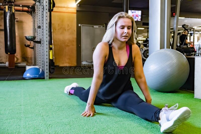 Νέα κατάλληλη γυναίκα στη γυμναστική που κάνει την μπροστινή διασπασμένη άσκηση θηλυκό στοκ εικόνα με δικαίωμα ελεύθερης χρήσης