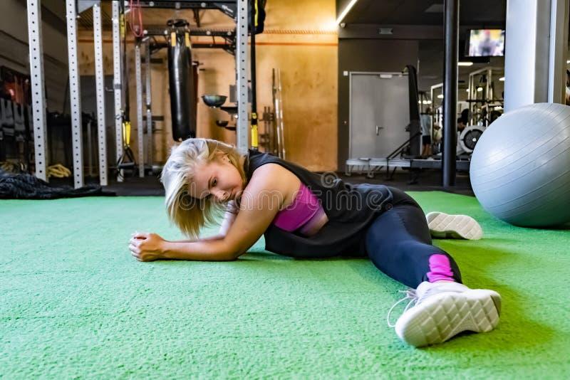 Νέα κατάλληλη γυναίκα στη γυμναστική που κάνει τη διασπασμένη άσκηση θηλυκό αθλητών στοκ εικόνες