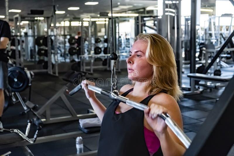 Νέα κατάλληλη γυναίκα στη γυμναστική που κάνει pulldown την άσκηση με το βάρος μ στοκ φωτογραφία με δικαίωμα ελεύθερης χρήσης