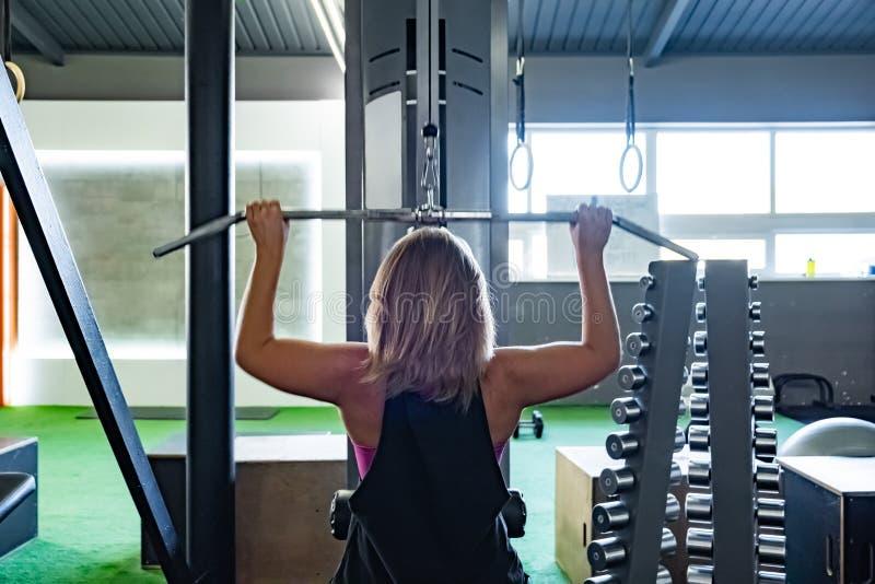 Νέα κατάλληλη γυναίκα στη γυμναστική που κάνει pulldown την άσκηση με το βάρος μ στοκ εικόνα