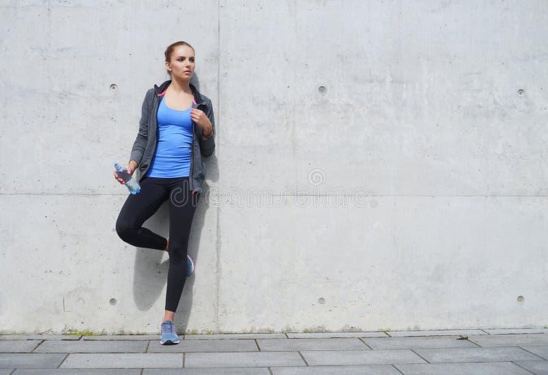 Νέα, κατάλληλη και φίλαθλη γυναίκα που στέκεται μπροστά από το συγκεκριμένο τοίχο τσιμέντου Ικανότητα, αθλητισμός, αστικό και υγι στοκ φωτογραφία