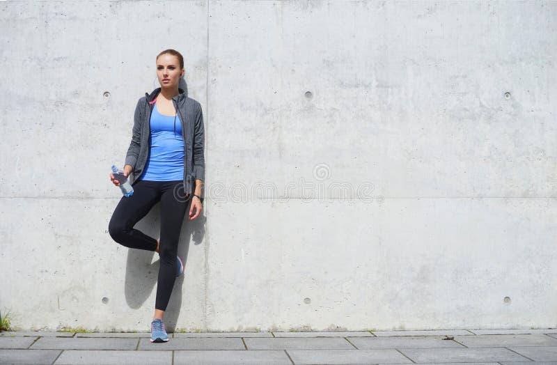 Νέα, κατάλληλη και φίλαθλη γυναίκα που στηρίζεται μετά από την κατάρτιση Ικανότητα, αθλητισμός, αστικό και υγιής έννοια τρόπου ζω στοκ εικόνες