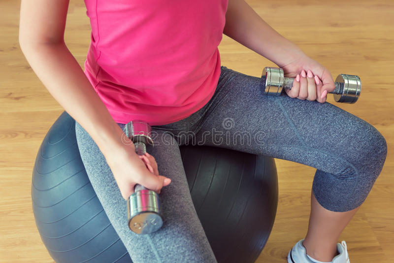 Download Νέα κατάρτιση γυναικών στη γυμναστική με τους αλτήρες, που κάθονται στο Fitball Στοκ Εικόνες - εικόνα από ελεύθερος, ισχυρός: 62701764