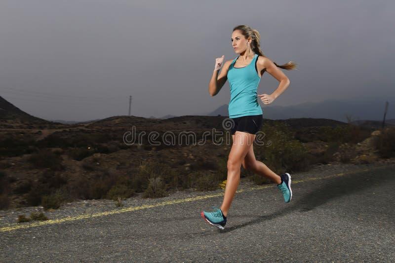 Νέα κατάλληλη αθλήτρια που τρέχει υπαίθρια στο δρόμο ασφάλτου στην ικανότητα βουνών workout στοκ εικόνα