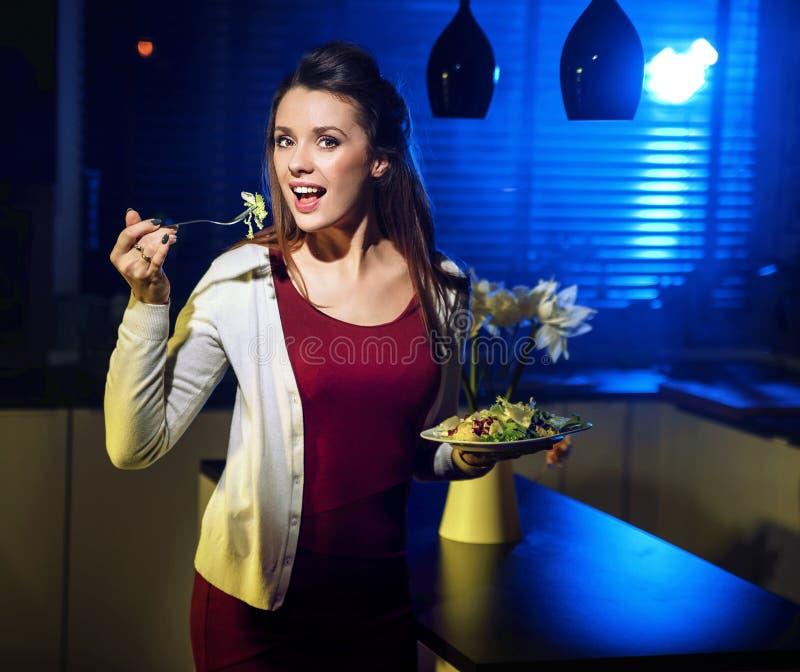 Νέα κατάλληλη κυρία που τρώει την ελαφριά σαλάτα στοκ φωτογραφία