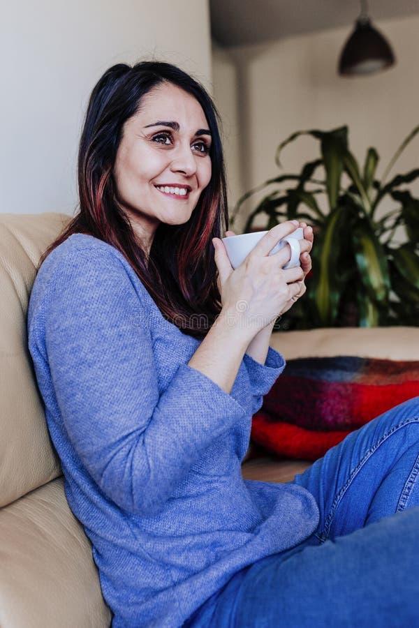 νέα καυκάσια γυναίκα που έχει τον καφέ ή το τσάι στο σπίτι για το πρόγευμα στο σπίτι Κλείστε επάνω την όψη στοκ φωτογραφία