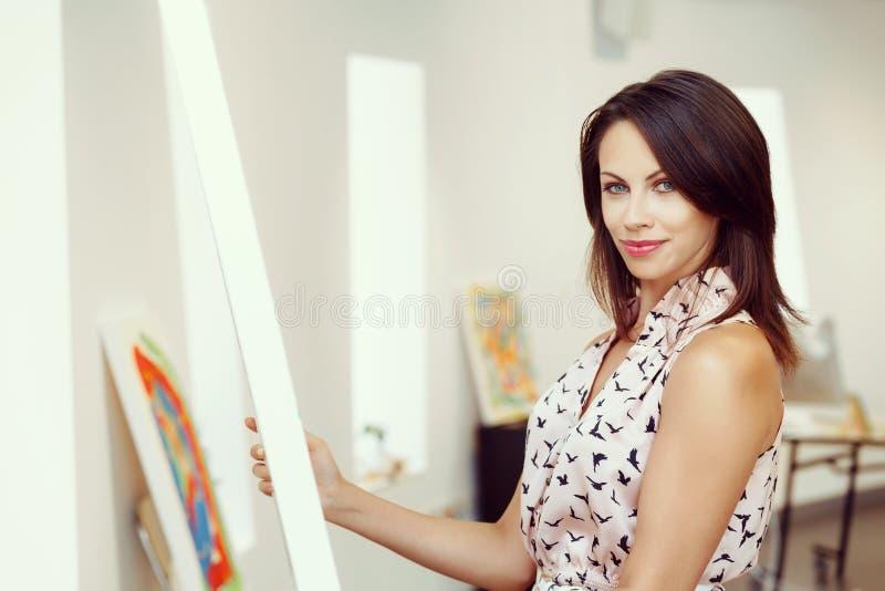 Νέα καυκάσια γυναίκα που στέκεται στο μέτωπο γκαλεριών τέχνης των έργων ζωγραφικής στοκ εικόνες