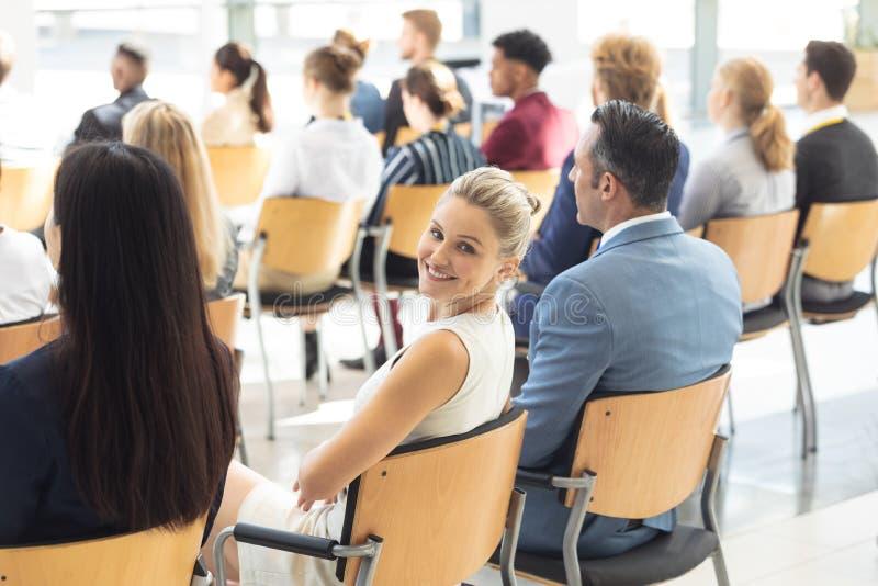 Νέα καυκάσια επιχειρηματίας που κάθεται στη αίθουσα συνδιαλέξεων, που χαμογελά στη κάμερα στοκ φωτογραφία με δικαίωμα ελεύθερης χρήσης
