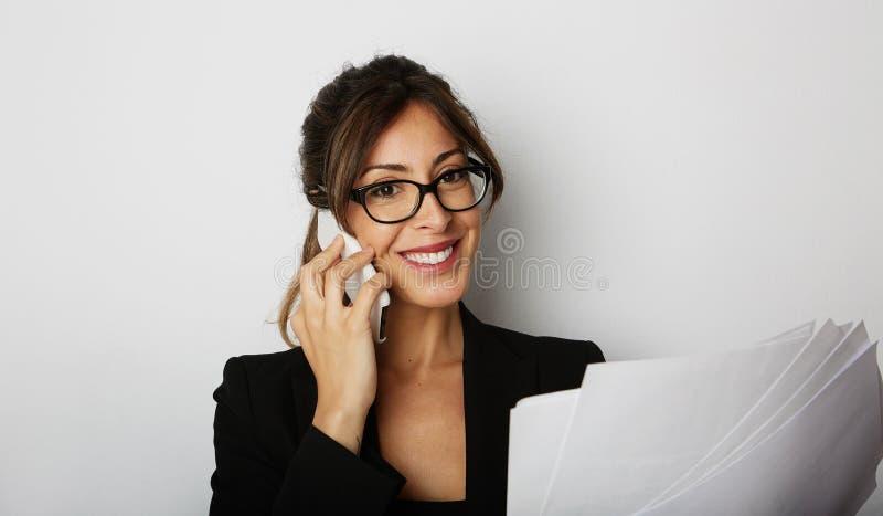 Νέα καυκάσια ευτυχής θηλυκή γυναίκα που χρησιμοποιεί την κινητή τηλεφωνική συνεδρίαση στον πίνακα πέρα από το κενό άσπρο υπόβαθρο στοκ φωτογραφία με δικαίωμα ελεύθερης χρήσης