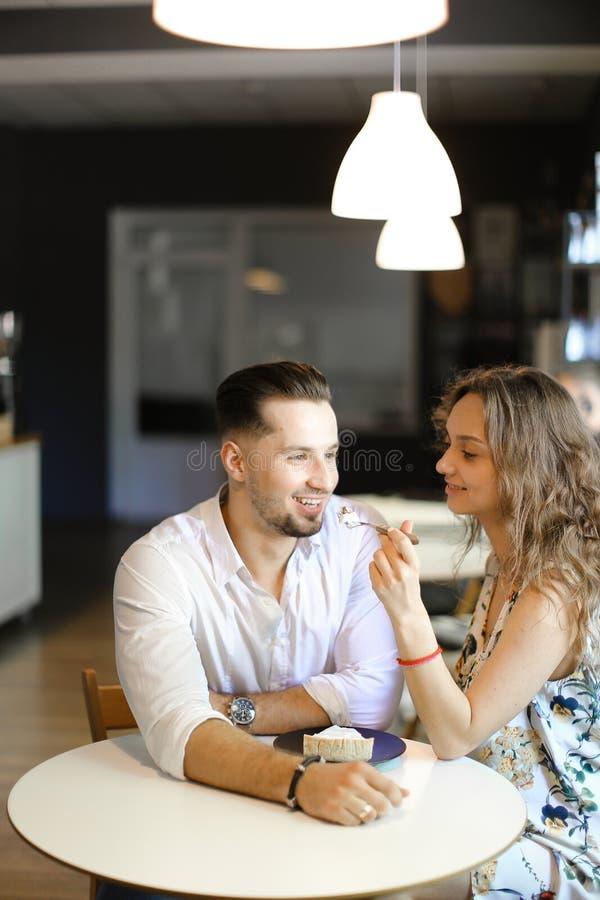 Νέα καυκάσια συνεδρίαση ατόμων με το κορίτσι στον καφέ στοκ εικόνα
