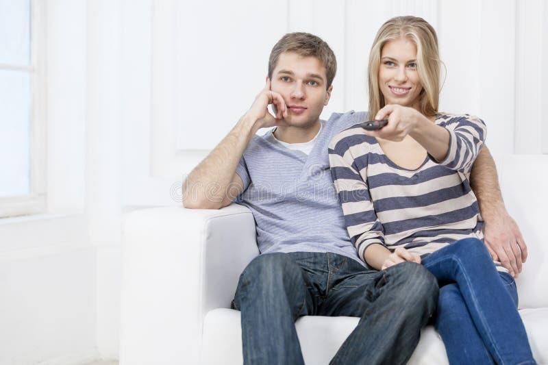 Νέα καυκάσια συνεδρίαση ζευγών στον καναπέ στοκ εικόνες