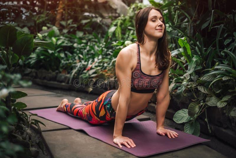 Νέα καυκάσια τεντώνοντας άσκηση γιόγκας άσκησης γυναικών στο βοτανικό κήπο στοκ φωτογραφίες με δικαίωμα ελεύθερης χρήσης