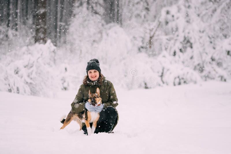 Νέα καυκάσια τοποθέτηση γυναικών κοριτσιών με το σκυλί κουταβιών το χειμώνα Fores στοκ εικόνες