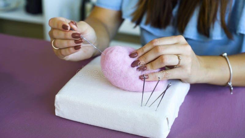 Νέα καυκάσια χέρια γυναικών κινηματογραφήσεων σε πρώτο πλάνο που κατασκευάζουν το μαλλί το ξηρό σεμινάριο πίλησης στοκ εικόνα με δικαίωμα ελεύθερης χρήσης
