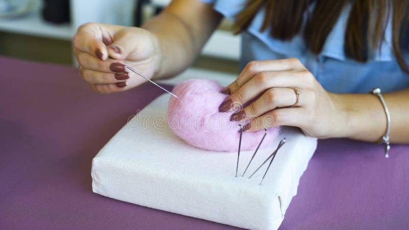 Νέα καυκάσια χέρια γυναικών κινηματογραφήσεων σε πρώτο πλάνο που κατασκευάζουν το μαλλί το ξηρό σεμινάριο πίλησης στοκ φωτογραφία με δικαίωμα ελεύθερης χρήσης