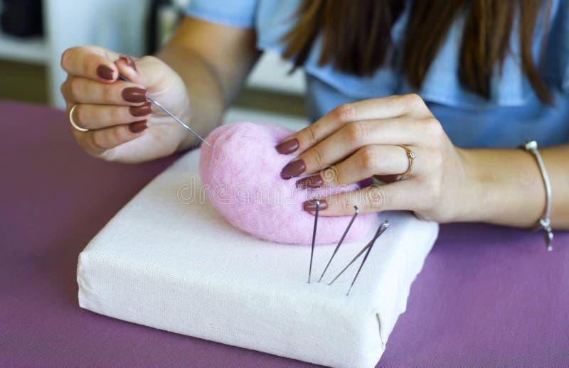 Νέα καυκάσια χέρια γυναικών κινηματογραφήσεων σε πρώτο πλάνο που κατασκευάζουν το μαλλί το ξηρό σεμινάριο πίλησης στοκ εικόνες