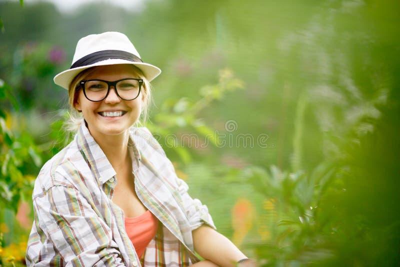 Νέα καυκάσια χαμογελώντας γυναίκα που φροντίζει για τις εγκαταστάσεις στον κήπο της στοκ εικόνα με δικαίωμα ελεύθερης χρήσης