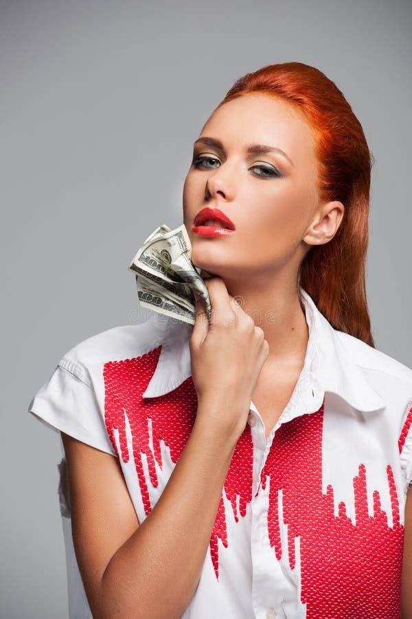 Νέα καυτή γυναίκα με τα δολάρια στο γκρίζο υπόβαθρο στοκ εικόνα με δικαίωμα ελεύθερης χρήσης