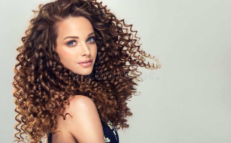Νέα, καφετιά μαλλιαρή γυναίκα με τις πυκνές, ανοιξιάτικες, ελαστικές μπούκλες σε ένα hairstyle στοκ εικόνες