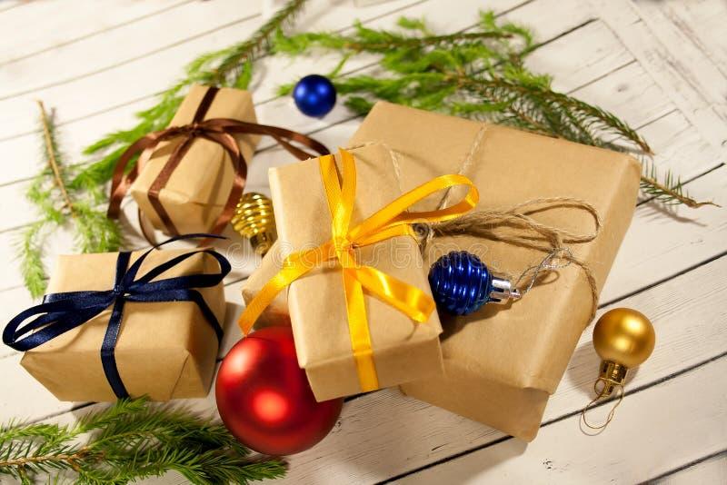 Νέα κιβώτια δώρων έτους και Χριστουγέννων στο αγροτικό ύφος σε ένα ξύλινο wh στοκ φωτογραφία με δικαίωμα ελεύθερης χρήσης
