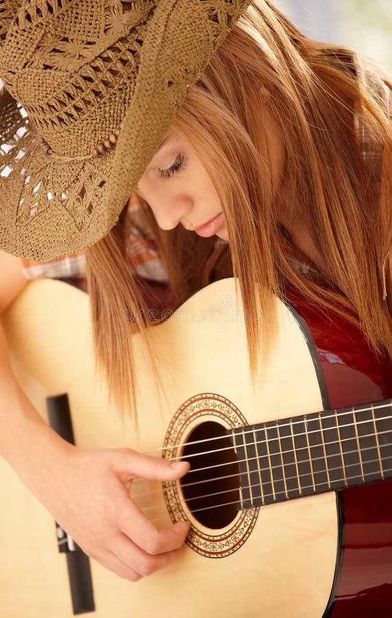 Νέα κιθάρα παιχνιδιού γυναικών με την έκφραση στοκ φωτογραφίες