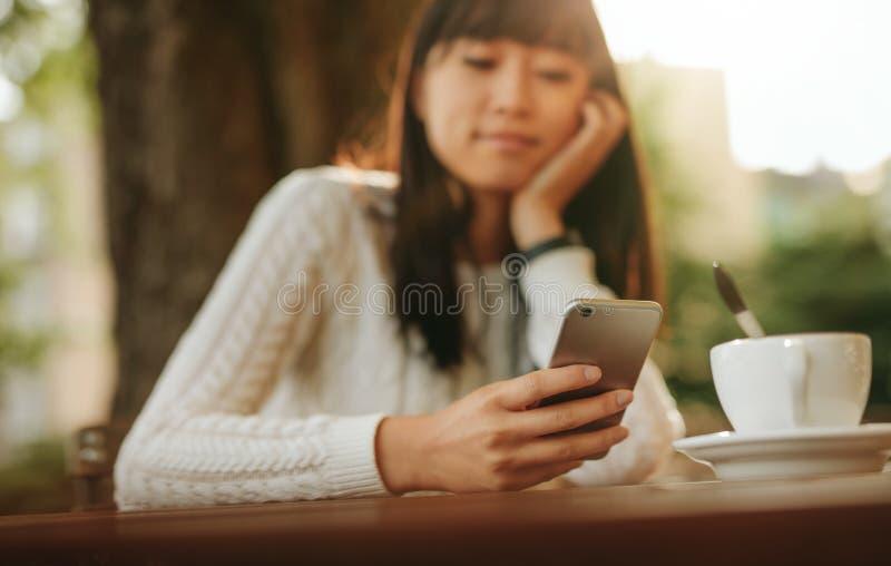 Νέα κινεζική γυναίκα που χρησιμοποιεί το κινητό τηλέφωνο στον υπαίθριο καφέ στοκ φωτογραφίες