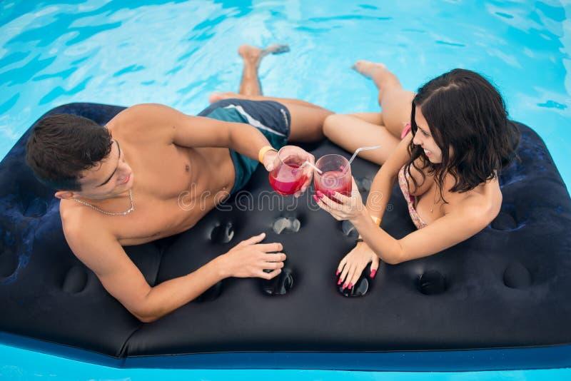 Νέα κοκτέιλ κατανάλωσης ζευγών σε ένα στρώμα στην πισίνα που απολαμβάνει η μια την άλλη και καλοκαιρινές διακοπές, τοπ άποψη στοκ εικόνες