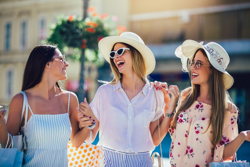 Νέα κορίτσια που περπατούν την οδό με τις τσάντες αγορών Ευτυχείς αγορές με τα χαμόγελα στοκ φωτογραφία