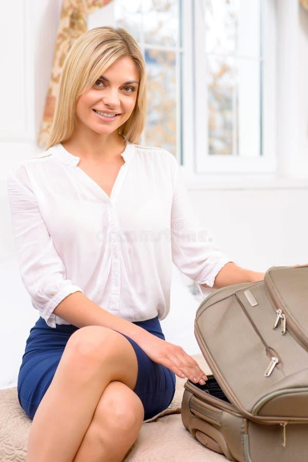 Νέα κυρία που ανοίγει τις αποσκευές της στοκ φωτογραφίες