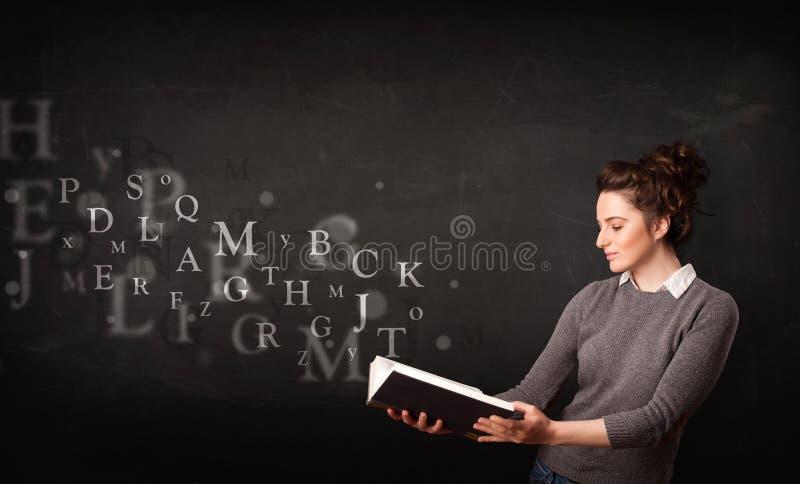 Νέα κυρία που διαβάζει ένα βιβλίο με τις επιστολές αλφάβητου στοκ εικόνες