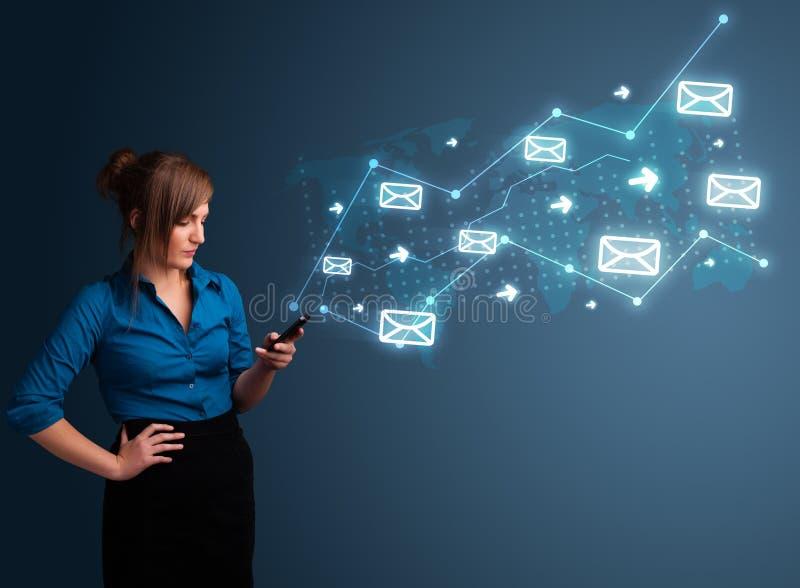 Νέα κυρία που κρατά ένα τηλέφωνο με τα βέλη και τα εικονίδια μηνυμάτων στοκ φωτογραφίες