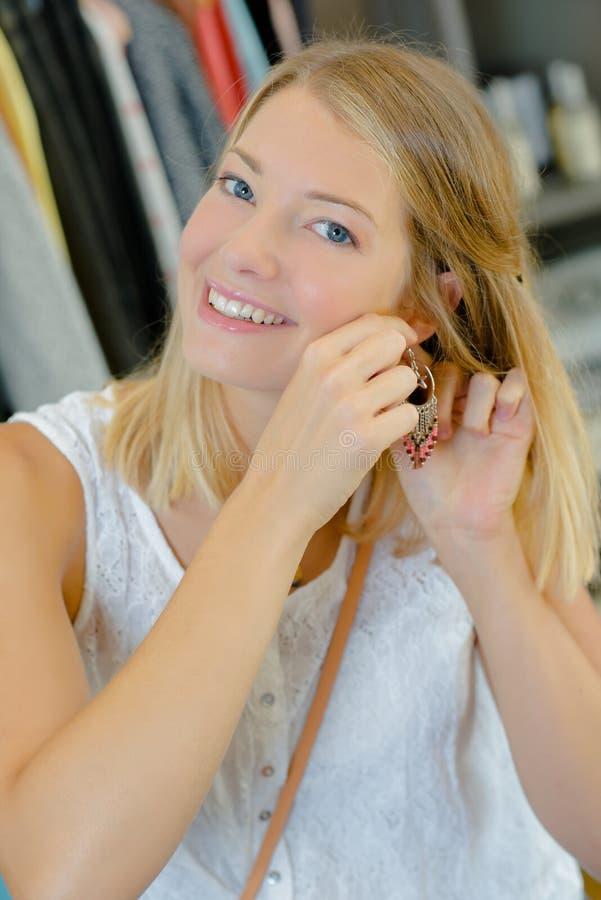 Νέα κυρία που προσπαθεί στο σκουλαρίκι στοκ φωτογραφίες με δικαίωμα ελεύθερης χρήσης