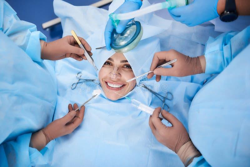 Νέα κυρία που χαμογελά περιβάλλων από τους χειρούργους στοκ εικόνες με δικαίωμα ελεύθερης χρήσης