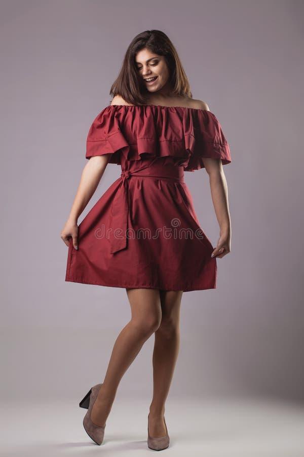 Νέα κυρία brunette στην κόκκινη τοποθέτηση φορεμάτων στο γκρίζο υπόβαθρο στοκ φωτογραφία με δικαίωμα ελεύθερης χρήσης