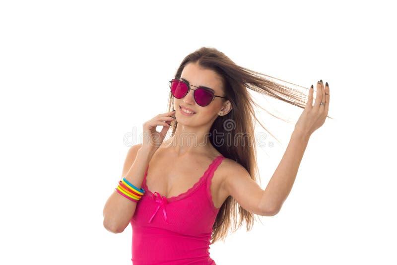 Νέα κυρία Cutie με τη σκοτεινή τρίχα στο ρόδινο θερινό πουκάμισο και χαμόγελο γυαλιών ηλίου που απομονώνεται στο άσπρο υπόβαθρο στοκ εικόνες με δικαίωμα ελεύθερης χρήσης