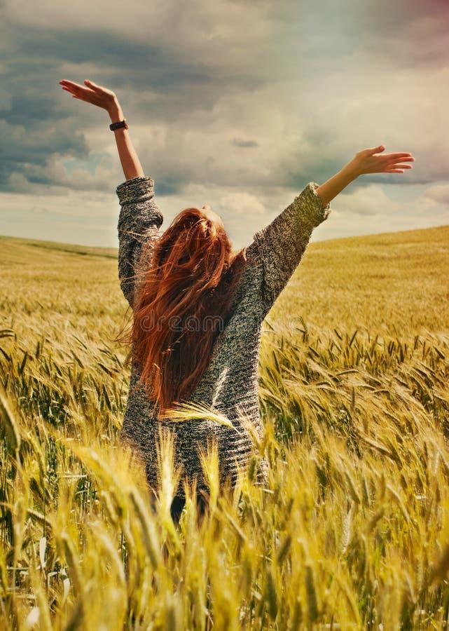 Νέα κόκκινη γυναίκα τρίχας που στέκεται τα πίσω χέρια μέχρι τη συναρπαστική άποψη στοκ εικόνες