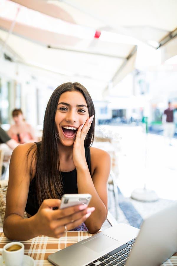 Νέα λατινική γυναίκα που παίρνει συγκλονισμένη από τις ειδήσεις στο τηλέφωνό της υπαίθρια στον καφέ Συγκλονισμένο πρόσωπο μιας συ στοκ φωτογραφία με δικαίωμα ελεύθερης χρήσης