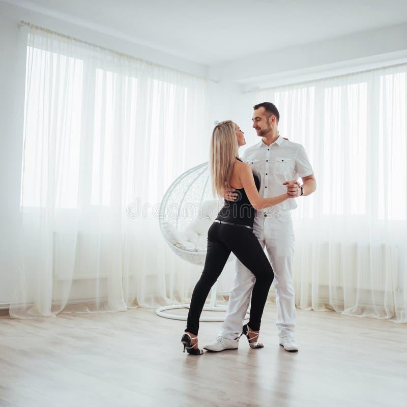 Νέα λατινική μουσική χορού ζευγών: Bachata, merengue, salsa Η κομψότητα δύο θέτει στο άσπρο δωμάτιο στοκ φωτογραφία