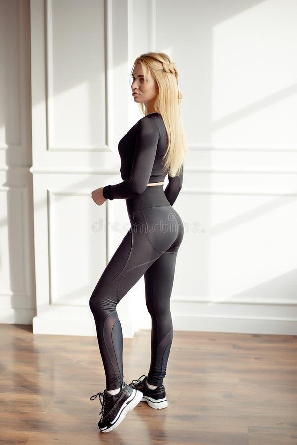 Νέα λεπτή γυναίκα με μια αθλητική μακριά ξανθή τρίχα σωμάτων που φορά στη μαύρη αθλητικό sportswear κορυφή και τη στάση περικνημί στοκ φωτογραφία με δικαίωμα ελεύθερης χρήσης