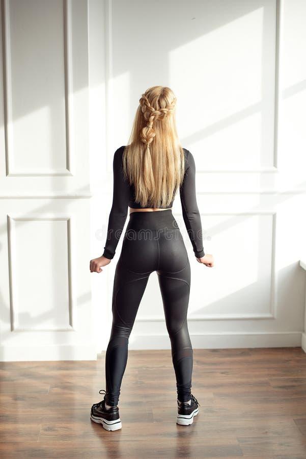 Νέα λεπτή γυναίκα με μια αθλητική ξανθή τρίχα σωμάτων που φορά στη μαύρη αθλητική κορυφή και περικνημίδες που στέκονται στο φωτει στοκ φωτογραφίες με δικαίωμα ελεύθερης χρήσης