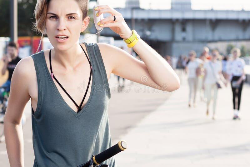 Νέα λεπτή γυναίκα με το σύντομο κούρεμα στο ποδήλατο με τα ακουστικά στοκ εικόνα με δικαίωμα ελεύθερης χρήσης