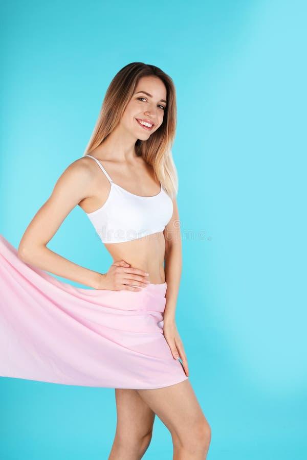 Νέα λεπτή γυναίκα που καλύπτει το σώμα της με το ύφασμα στο υπόβαθρο χρώματος στοκ φωτογραφία με δικαίωμα ελεύθερης χρήσης
