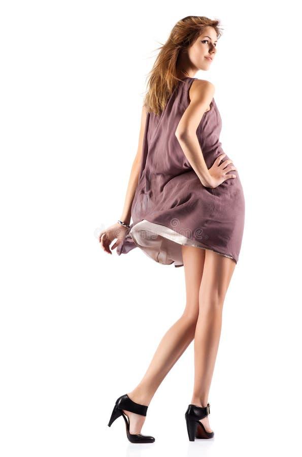 Νέα λεπτή γυναίκα στο κυματίζοντας φόρεμα στοκ φωτογραφία