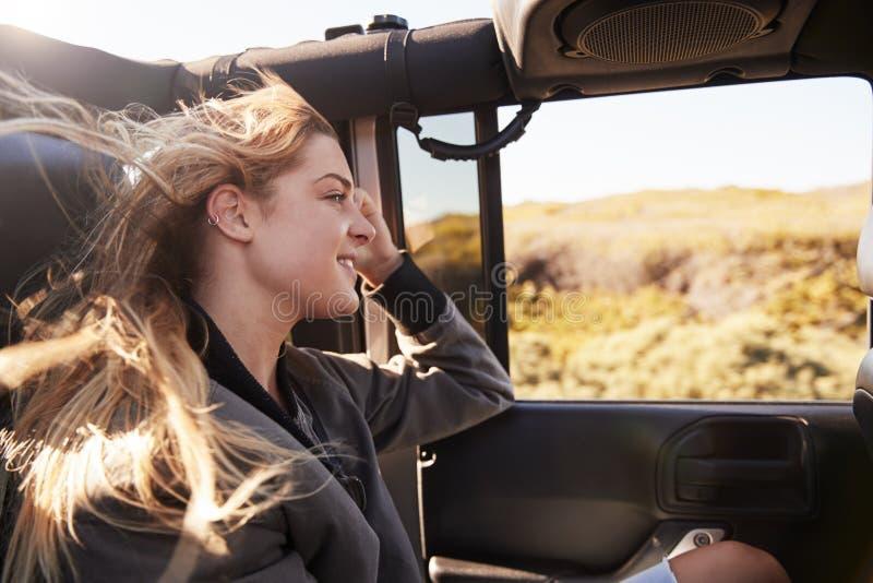Νέα λευκή γυναίκα που θαυμάζει το τοπίο από ένα ανοικτό αυτοκίνητο στοκ φωτογραφία με δικαίωμα ελεύθερης χρήσης