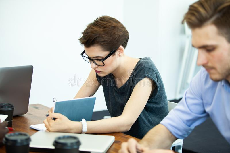 Νέα λύση κάθε μέρα Βέβαια νέα γυναίκα στην έξυπνη περιστασιακή ένδυση που εργάζεται στο lap-top καθμένος στη θέση εργασίας της στοκ φωτογραφία