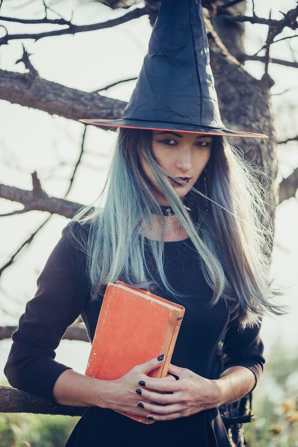 Νέα μάγισσα με το βιβλίο στοκ φωτογραφία