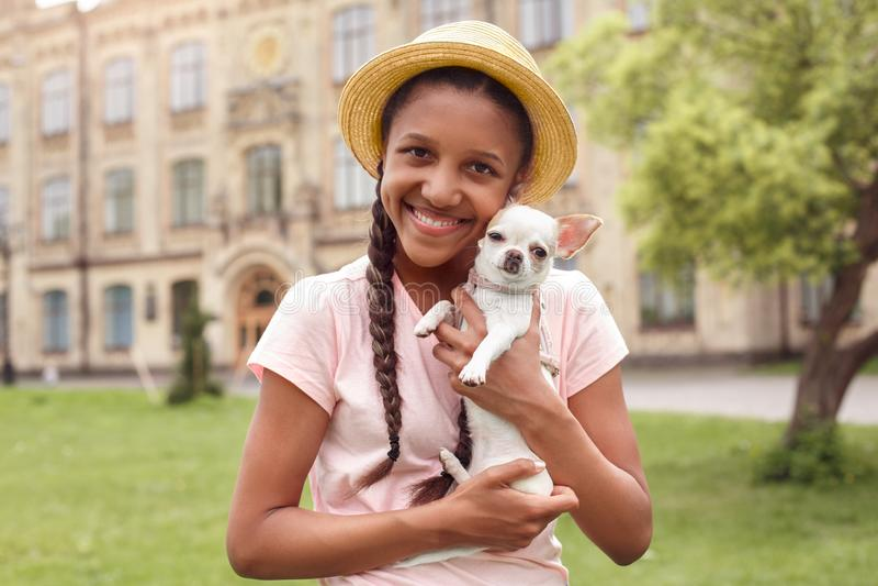 Νέα μαθήτρια στο καπέλο στο σχολικό ναυπηγείο που στέκεται με το κουτά στοκ εικόνες