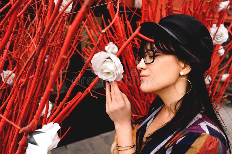 Νέα μακρυμάλλης γυναίκα brunette σε ένα φωτεινό φόρεμα ενάντια σε έναν κόκκινο τοίχο στοκ φωτογραφίες