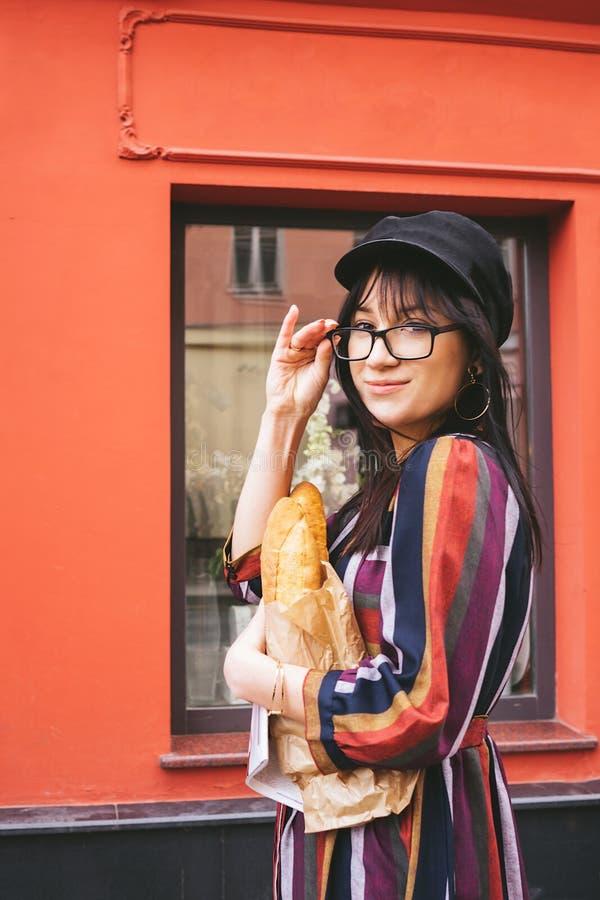 Νέα μακρυμάλλης γυναίκα brunette σε ένα φωτεινό φόρεμα ενάντια σε έναν κόκκινο τοίχο στοκ φωτογραφία με δικαίωμα ελεύθερης χρήσης