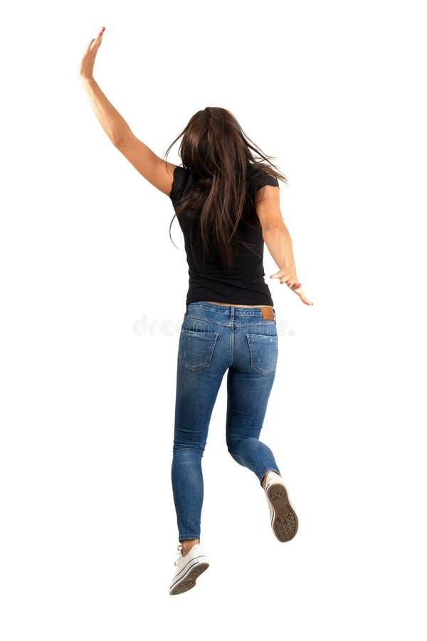 Νέα μακρυμάλλης γυναίκα που πηδά ή που τρέχει μακριά Όψη πίσω πλευρών στοκ εικόνα